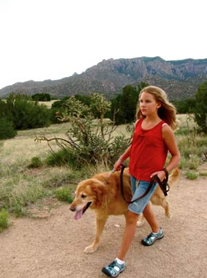 girl walking with with dog on trail